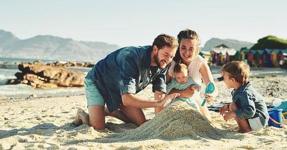 family building a sandcastle on the beach