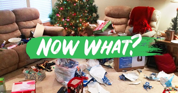 A living room decorated for Christmas is covered in torn wrapping paper and discarded ribbons.