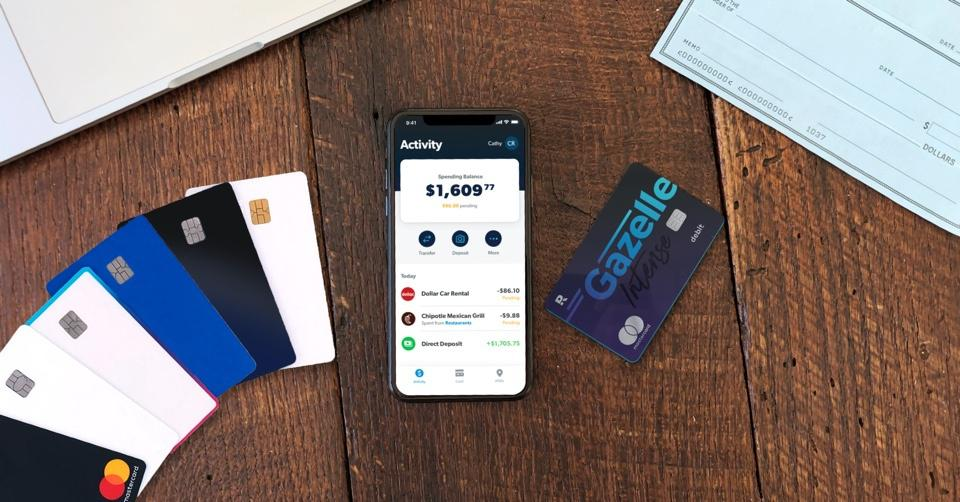 Several debit cards are on a table with smart phone showing a banking app.