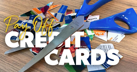 A pile of cut-up credit cards under a pair of scissors.
