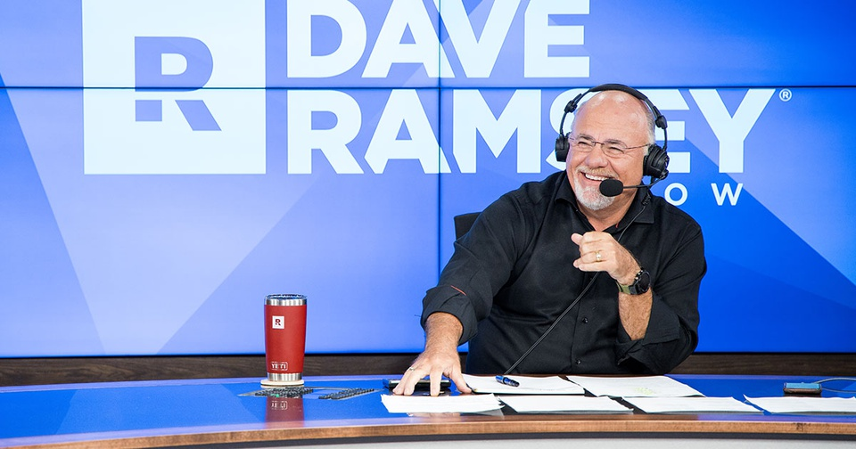 Dave Ramsey sitting at a desk hosting The Dave Ramsey Show