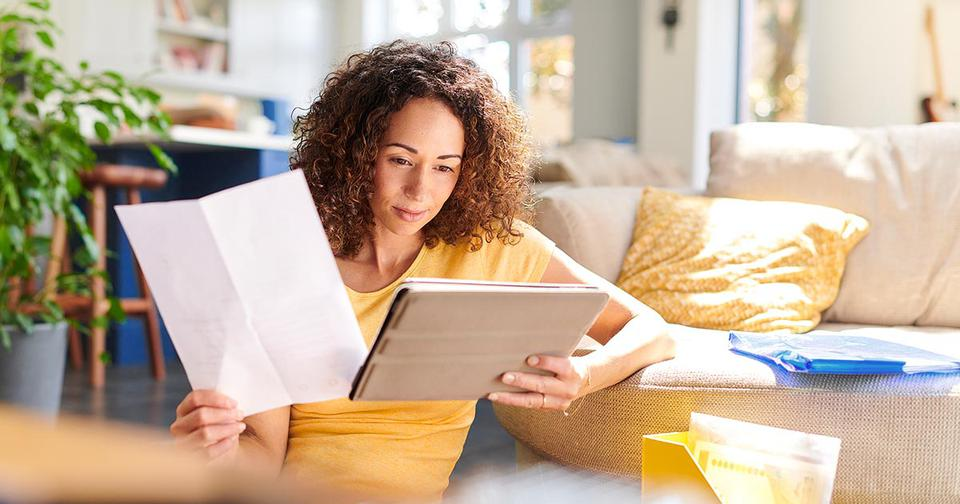 A woman reviews a tablet in her hand