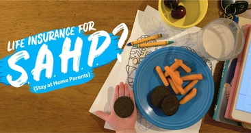 A snack plate of oreos and carrot sticks sits on top of coloring pages, and a small child's hand is holding a cookie.
