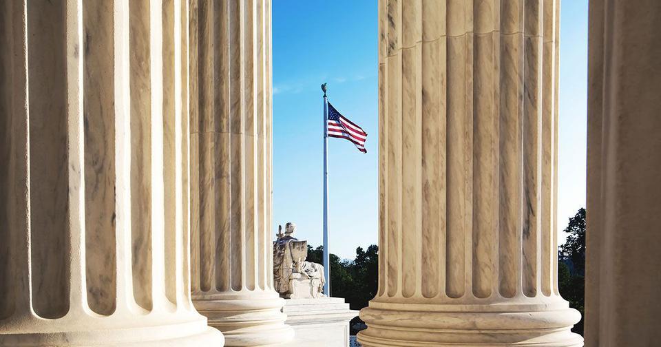Photo of American flag through columns