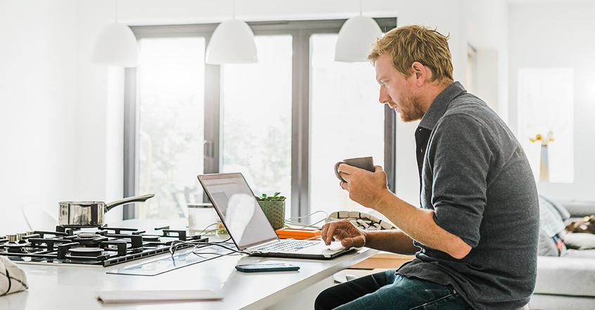 Middle aged man sitting in his kitchen drinking coffee and working on a computer