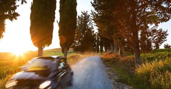 Black car driving down a road at sunset