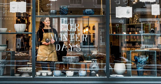 Business woman standing in the window of her boutique looking out