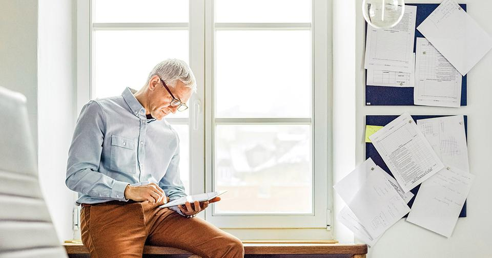 A older man sitting on a ledge looking at an ipad