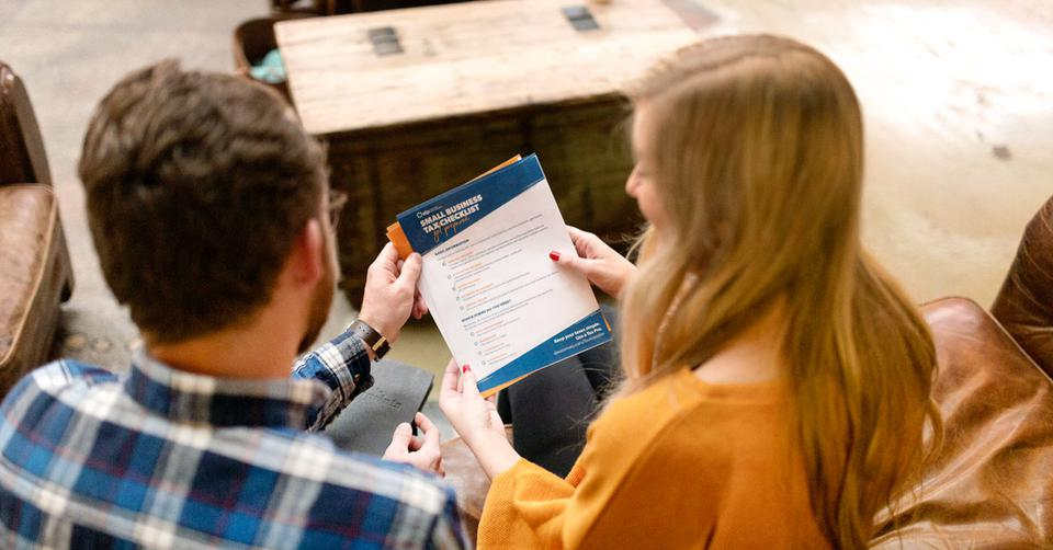 Two people looking at a tax checklist