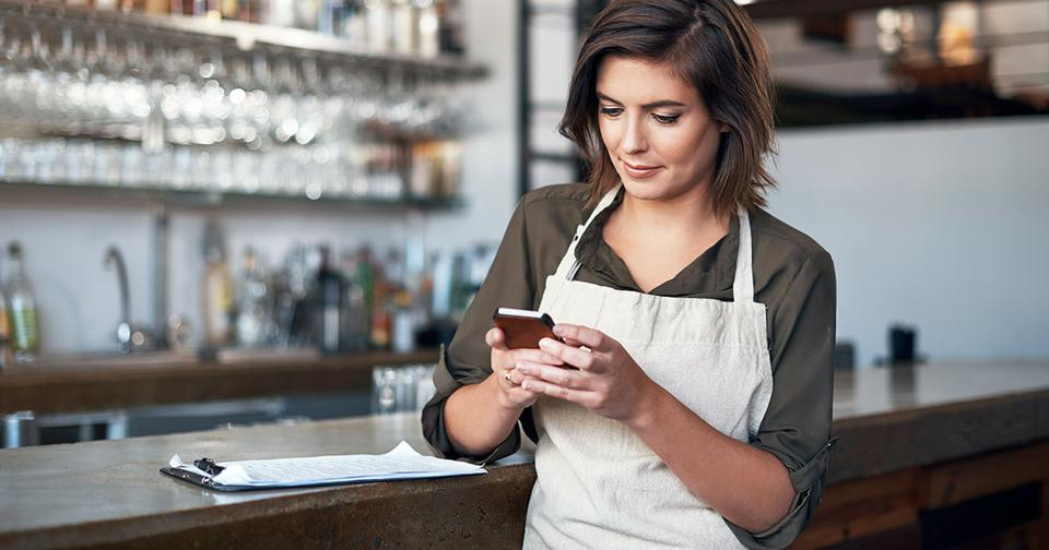 waitress at restaurant checking bank account on cell phone