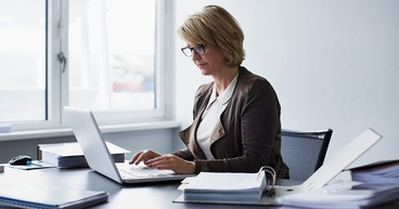 woman sits at desk working on laptop