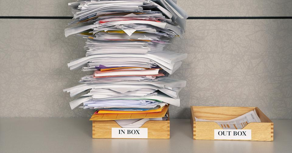 large stack of papers in inbox and small stack of papers in outbox