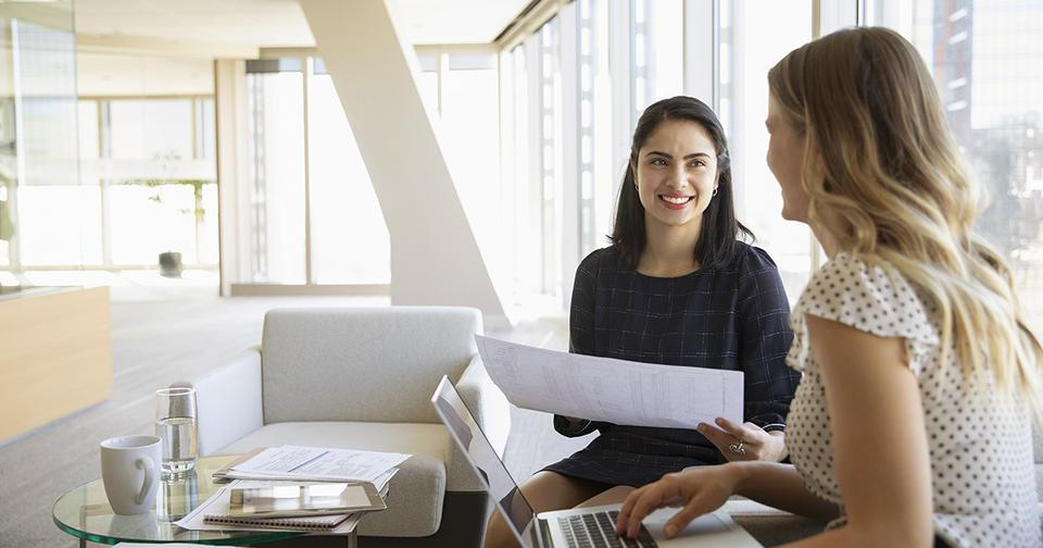 Two women in a meeting, one works on a computer and the other holds a piece of paper.