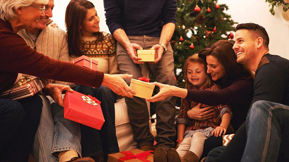 A family gathered in a close circle handing out gifts