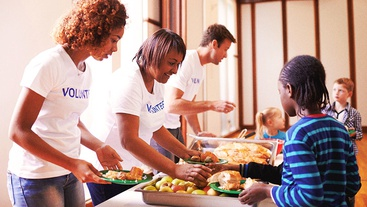 Three people with volunteer shirts standing in a line put together plates of food for children