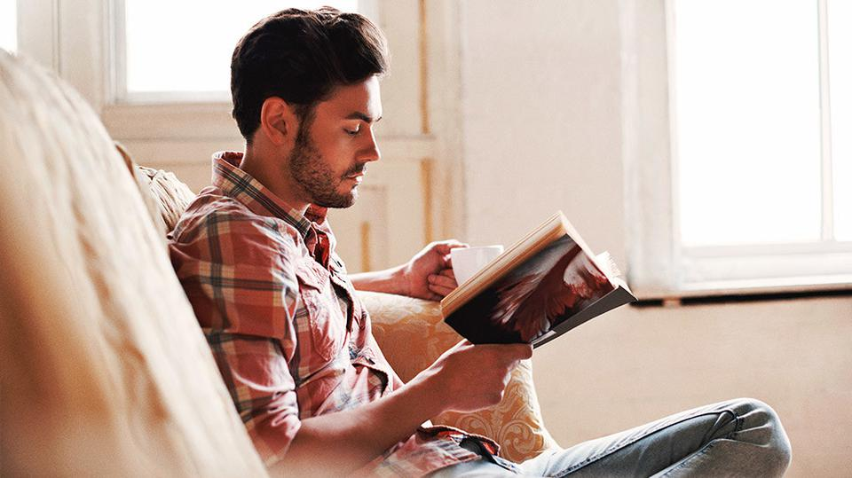 A man sitting on a couch with a cup of coffee and a book