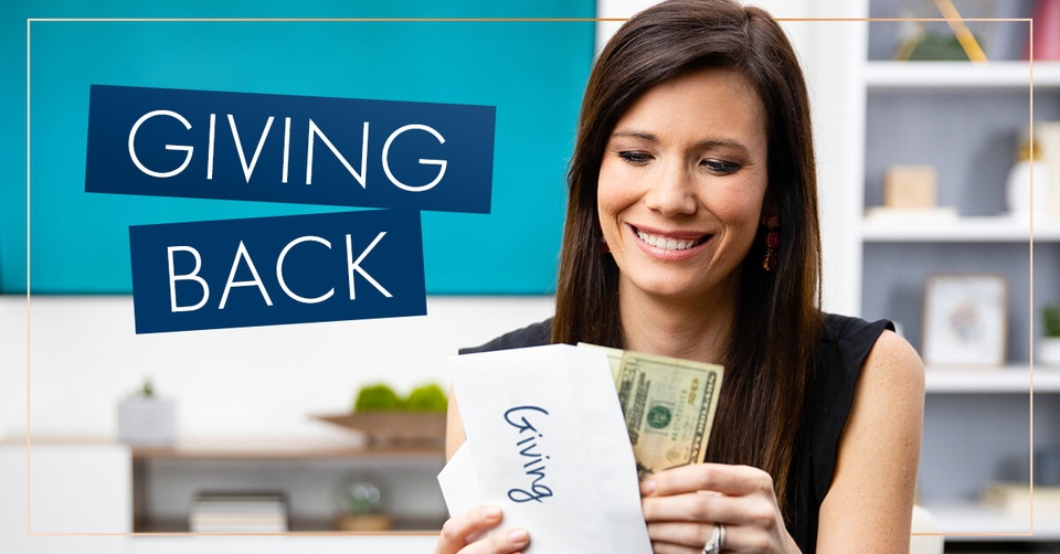 Rachel Cruze holding an envelope labeled giving with money coming out.