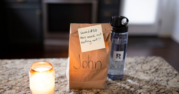 A lunch sack with a sticky-note encouraging a man to save money to pay off his mortgage early.