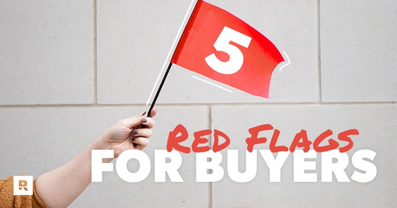 A person holding out a red flag symbolizing the red flags for home inspectors.