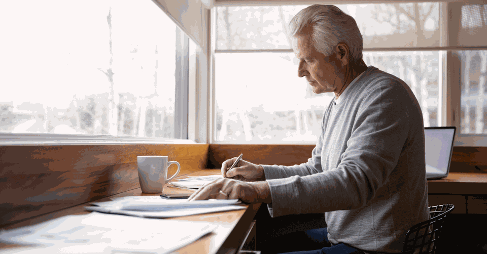 A man sits at a counter reviewing papers in front of him.